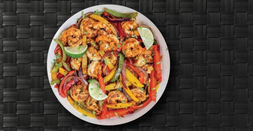 Picture of Shrimp Fajitas Plated on White China Plate with Veggies and Garnish