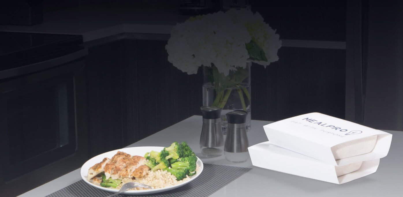 MealPro fitness meals laid out on kitchen island with mealpro packaging on the side
