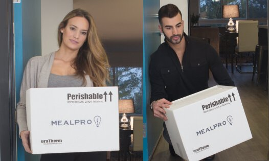 A woman and man holding a MealPro box at their house
