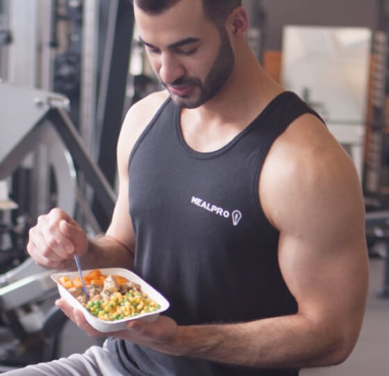 person sitting on a gym bench eating delicious fitness food