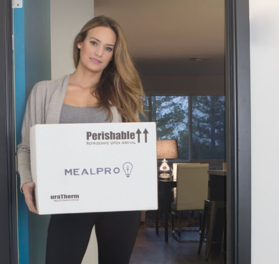 Person holding the MealPro box at the door