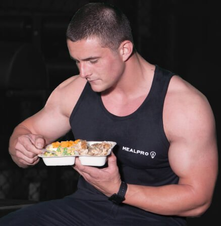 Buff Athlete Sitting On a Gym Bench Wearing A MealPro Tee Eating a Fitness Meal