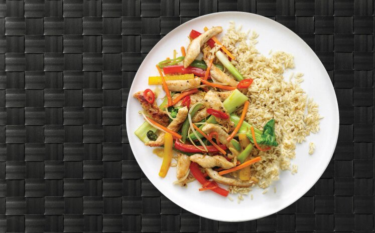 Picture shows a chicken high protein meal with brown rice and fresh veggies