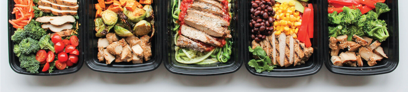 Healthy   meals being plated in meal prep containers